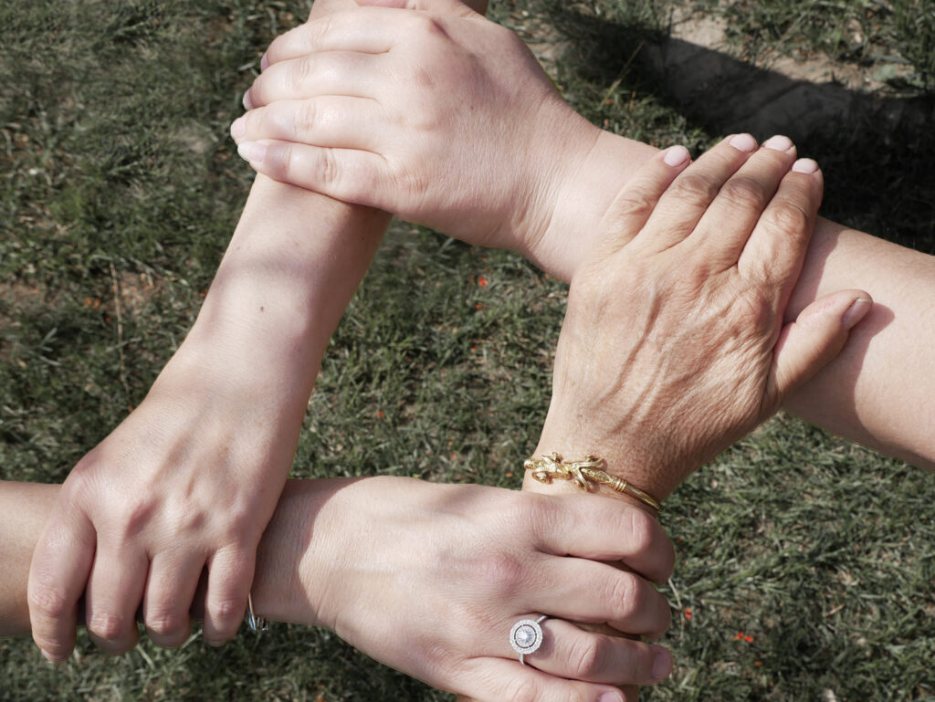 Vier Personen reichen sich die Hände und geben sich Halt