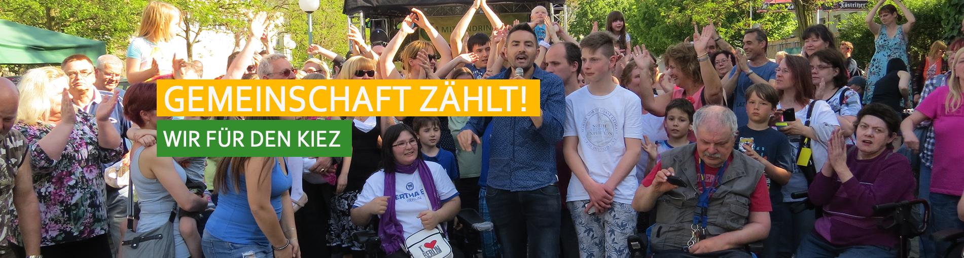 Gemeinwesen: Menderes singt vor einer Gruppe Menschen in Hellersdorf