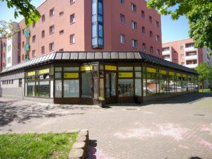 Beschäftigungstagesstätte von außen: Roter Neubau mit 5 Stockwerken. Im Erdgeschoss die BTS als Anbau über eine Ecke mit kompletter Fensterfront