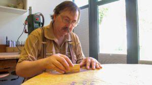 Beschäftigungstagesstätte: Ein Mann sitzt an einem Tisch und schleift ein Stück Holz mit Schleifpapier