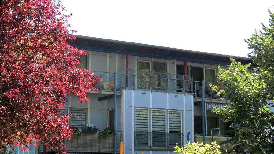 TWG Waldowpark von außen. Wohnhaus mit flachem Dach und hellblauer Fassade. Davor ein roter Baum