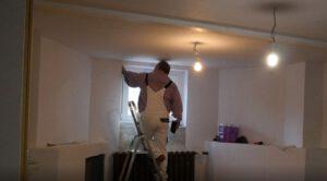 Zuverdient: Mann steht auf einer Leiter in einem Kellerraum und streicht den Fensterrahmen