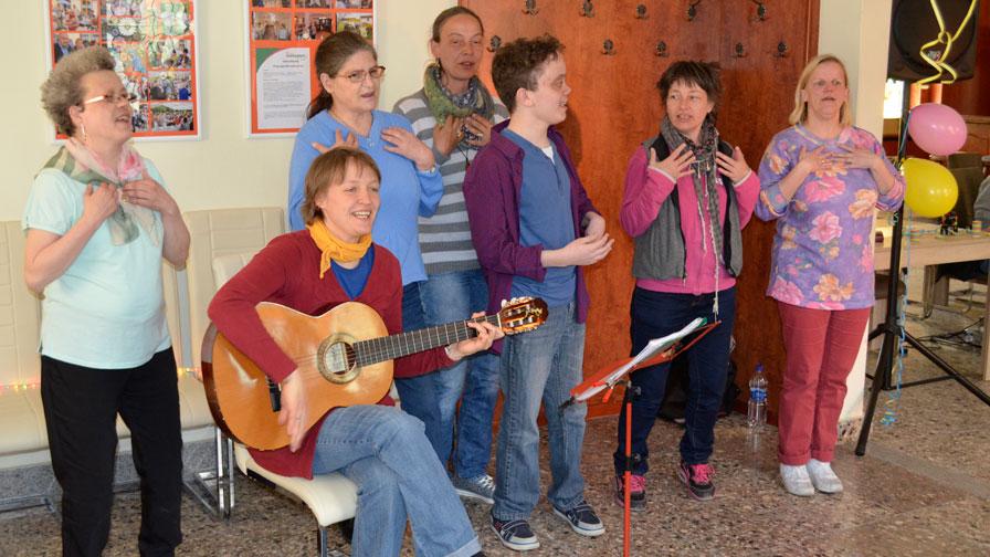 Singegruppe: 6 Sängerinnen und Sänger stehen vor einer Holzwand und singen. Zusätztlich sitzt eine Gitarrenspielerin auf einem Stuhl