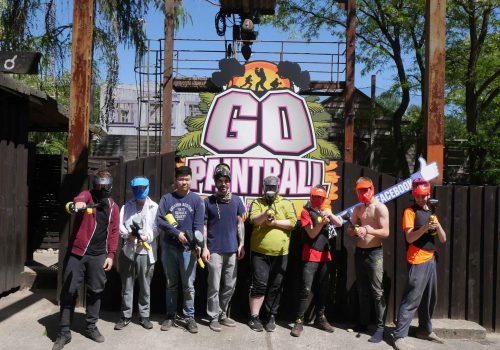 """8 Personen beim Paintball. Alle stehen mit Maske und ihren Markierern vor einem großen Schild auf den """"Go Paintball"""" steht"""