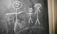 Kreidetafel auf der 3 Strichmännchen als Familie mit Kinder gemalt wurden