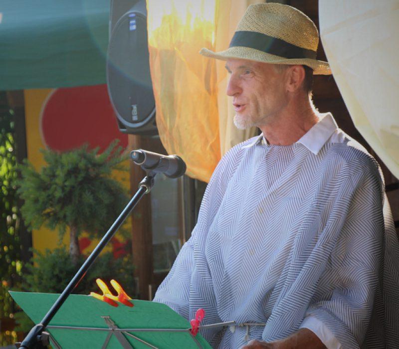 Theatergruppenleiter Martin Karl steht an einem Pult mit Mikrofon