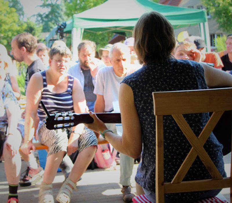 Singegruppe: Eine Person sitzt auf einem Stuhl und spielt eine Gitarre. Wir sehen sie von hinten mit Blick zum Publikum
